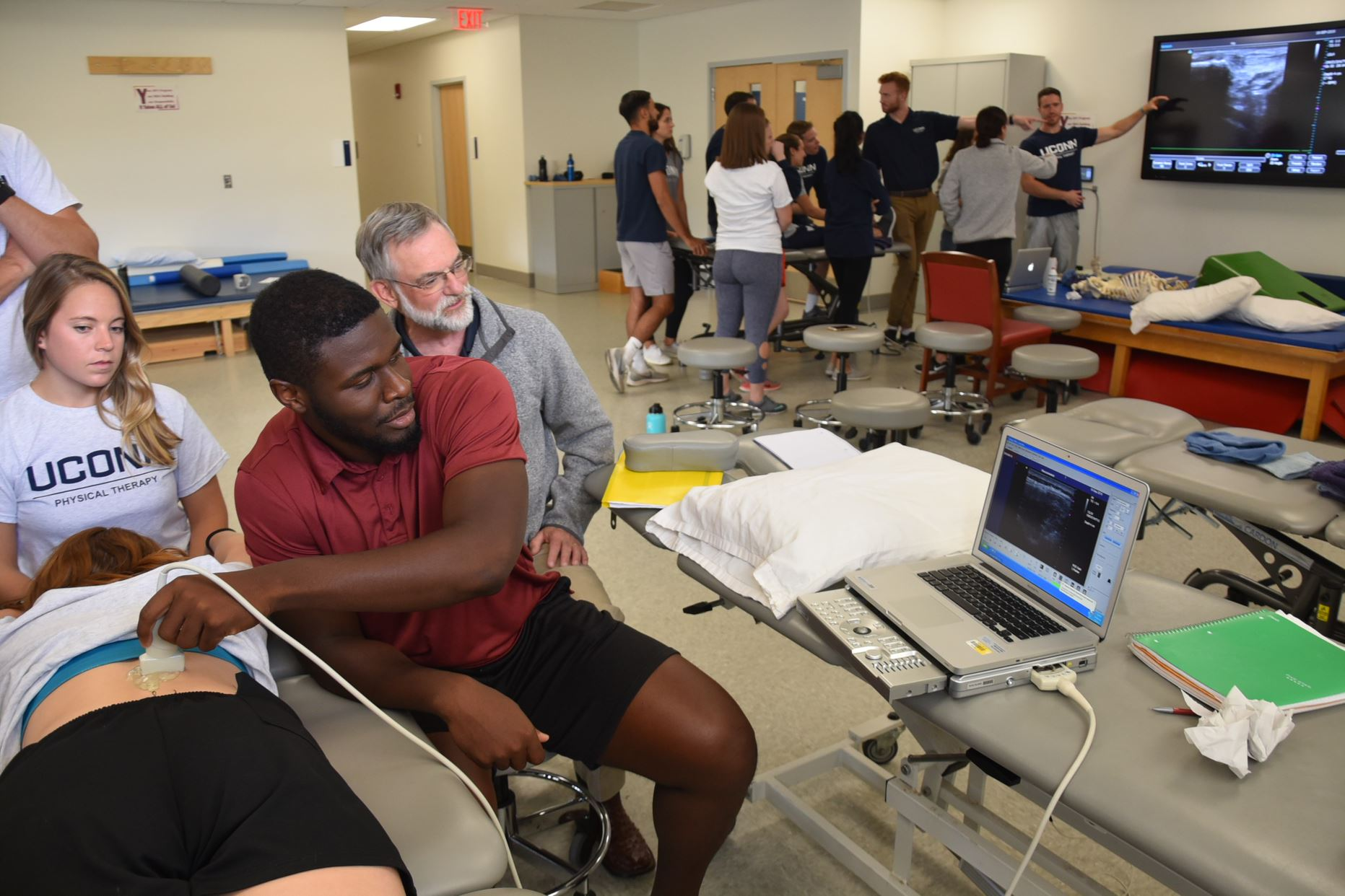 student practices an ultrasound on a classmate while faculty provide guidance